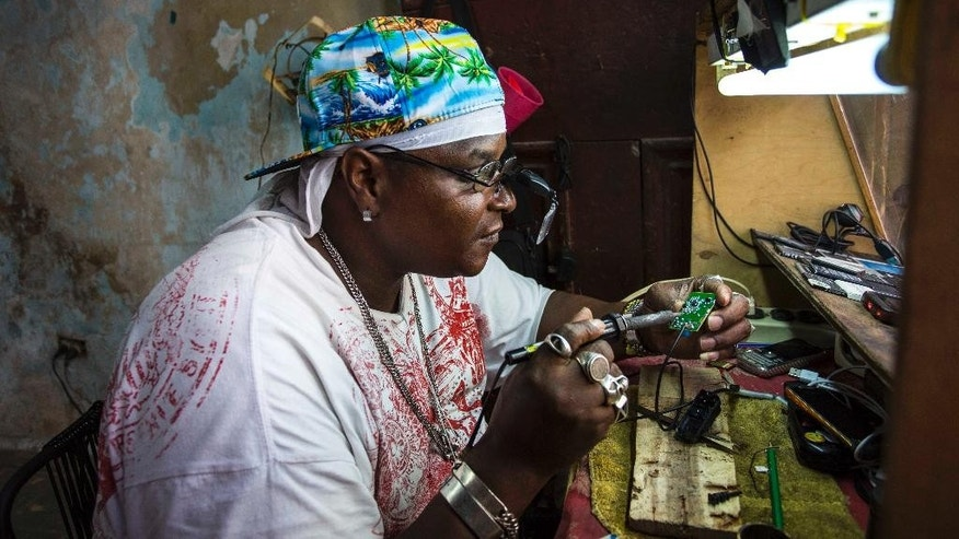 "Private jeweler and electronics technician Gabriel La O repairs a mobile phone inside a government store where he rents work space in Havana, Cuba, Tuesday, May 24, 2016. Cuba says it will legalize small and medium-sized private businesses by adding a category of small, mid-sized and ""micro"" private business to the Communist party's master plan for social and economic development. The government currently allows private enterprise by self-employed workers in several hundred job categories. (AP Photo/Desmond Boylan)"