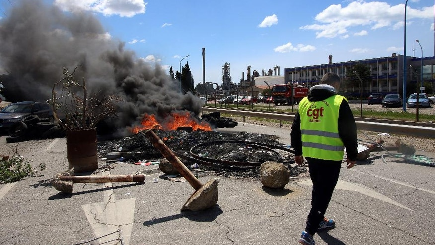 A striking workers walks past a burning barricade preventing the access to a refinery in Fos sur Mer, southern France, Monday, May 23, 2016. The union-led blockade, one of several set up at refineries and depots across France, is aimed at securing the withdrawal of the country's labor reforms, which hopes to inject new life into the country's rigid labor market. (AP Photo/Claude Paris)