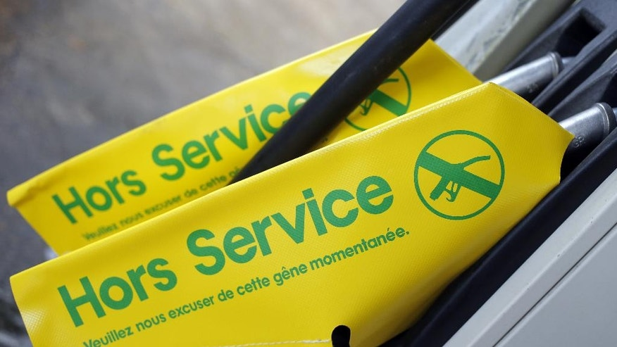 "A muff coffers a gas station fuel pipe reading ""Out of Service, Sorry For this Momentarily Embarrassment "" in a gaz station closed for fuel shortage in the15th district, in Paris, Monday, May 23, 2016. Union-led blockades of French depots and oil refineries have led to fuel shortages and police action. (AP Photo/Francois Mori)"