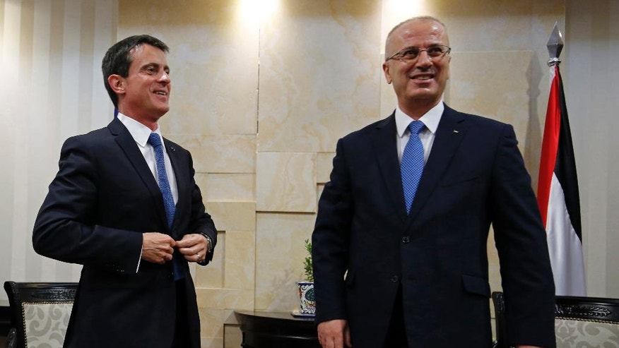 French Prime Minister Manuel Valls, left, meets with Palestinian Prime Minister Rami Hamdallah in the West Bank city of Ramallah, Tuesday, May 24, 2016. Valls is visiting the region in a bid to rouse support for a June conference in Paris in hopes of reviving the Israeli-Palestinian peace process. Israel and the Palestinians have not been invited, though the Palestinians have welcomed the French proposal. (Abbas Momani/Pool photo via AP)