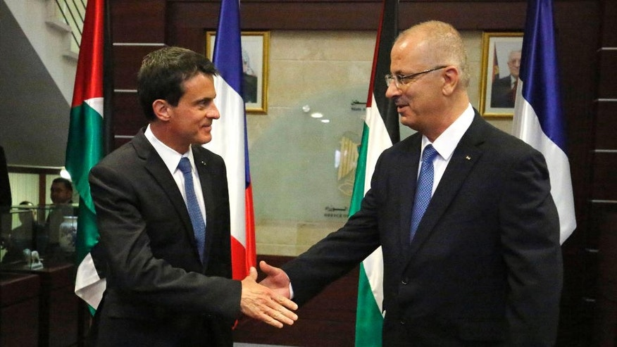 French Prime Minister Manuel Valls, left, shakes hands with Palestinian Prime Minister Rami Hamdallah in the West Bank city of Ramallah, Tuesday, May 24, 2016. Valls is visiting the region in a bid to rouse support for a June conference in Paris in hopes of reviving the Israeli-Palestinian peace process. Israel and the Palestinians have not been invited, though the Palestinians have welcomed the French proposal. (Abbas Momani/Pool Photo via AP)