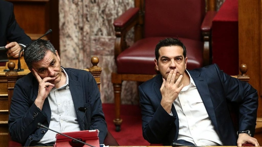 Greece's Prime Minister Alexis Tsipras, right, and Finance Minister Euclid Tsakalotos, attend a parliamentary session in Athens, Sunday, May 22, 2016.  Greek parliament votes on a bill ahead of a Eurogroup meeting next week which is likely to unlock bailout funds for the country. (AP Photo/ Yorgos Karahalis )