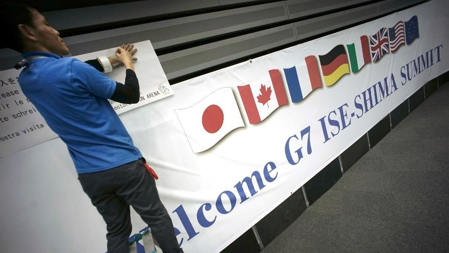 FILE - In this May 24, 2016 file photo, a man puts a banner of the G7 Summit at International Media Center in Ise, Mie Prefecture, central Japan. Leaders of the Group of Seven rich nations will undoubtedly voice unity over fighting terrorism, pandemics and tax evasion at their summit in Japan starting on Thursday, May 26. Finding a consensus on how to breathe life into their sluggish economies is proving more elusive. (AP Photo/Eugene Hoshiko, File)
