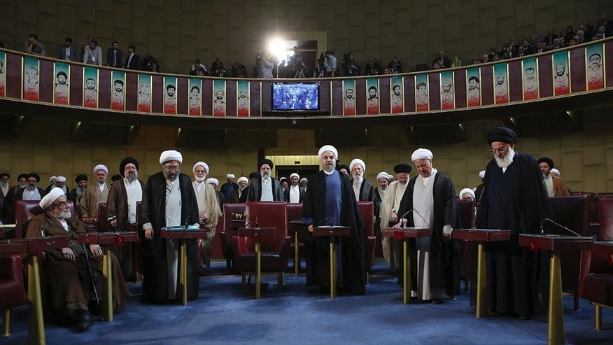 In this photo released by the official website of the office of the Iranian Presidency, members of Iran's Assembly of Experts stand while taking an oath during an inaugural meeting of the assembly in Tehran, Iran, Tuesday, May 24, 2016. A hard-line Iranian cleric was chosen on Tuesday as speaker of the Assembly of Experts, a clerical body that is mainly tasked with selecting the country's supreme leader. The official IRNA news agency said 89-year-old Ayatollah Ahmad Jannati won 51 votes in the 88-seat Assembly and would serve as speaker for the next two years. (Iranian Presidency Office via AP)