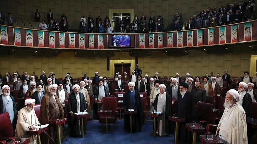 In this photo released by the official website of the office of the Iranian Presidency, members of Iran's Assembly of Experts and top officials stand while listening to the Iranian national anthem during inaugural meeting of the assembly in Tehran, Iran, Tuesday, May 24, 2016. A hard-line Iranian cleric was chosen on Tuesday as speaker of the Assembly of Experts, a clerical body that is mainly tasked with selecting the country's supreme leader. The official IRNA news agency said 89-year-old Ayatollah Ahmad Jannati won 51 votes in the 88-seat Assembly and would serve as speaker for the next two years. (Iranian Presidency Office via AP)