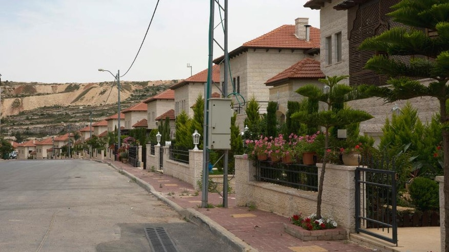 In this photo made Monday, May 9, 2016, a line of villas is seen in the Palestinian Diplomatic Neighborhood at the outskirts of the West Bank city of Ramallah. The gated community of villas with well-tended flower gardens near the West Bank town of Ramallah may help explain why Palestinians almost universally believe there is corruption in the government of President Mahmoud Abbas. (AP Photo/Nasser Nasser)