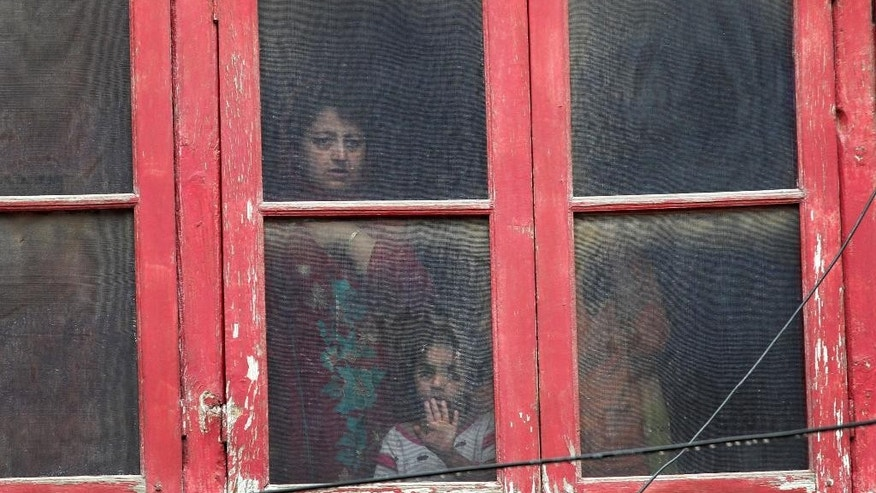 A Kashmiri family watches from the window of their house near the site of a gunbattle in Srinagar, Indian controlled Kashmir, Tuesday, May. 24, 2016. Indian police killed the operations head of a major militant group and his associate in the Indian portion of Kashmir in an overnight gunbattle, a police officer said Tuesday. (AP Photo/Mukhtar Khan)