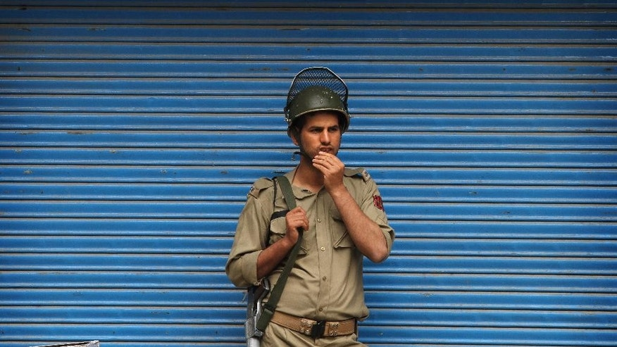 An Indian policeman guard is photographed near the site of a gunbattle in Srinagar, Indian controlled Kashmir, Tuesday, May. 24, 2016. Indian police killed the operations head of a major militant group and his associate in the Indian portion of Kashmir in an overnight gunbattle, a police officer said Tuesday. (AP Photo/Mukhtar Khan)