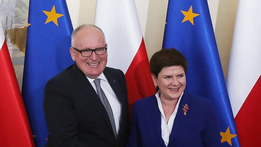 Poland's Prime Minister Beata Szydlo, right, and EU Commission Vice President Frans Timmermans, left, shake hands and smile before holding crucial talks on ways of ending Poland's political conflict that has strained ties with Brussels, at Szydlo's office in Warsaw, Poland, on Tuesday,  May  24, 2016. Alarmed by government moves that have paralysed the Constitutional Tribunal, the EU Commissions has threatened sanctions if the political conflict is not solved. Timmermans' meeting with Szydlo suggests that progress has been made in finding a solution.(AP Photo/Czarek Sokolowski)