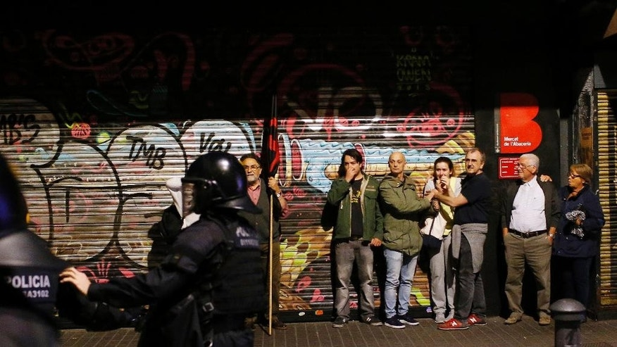 People react during clashes between protesters supporting squatters and police in Barcelona, Spain, Tuesday, May 24, 2016. Protesters clashed with police again Tuesday, less than 24 hours after demonstrators set trash containers and vehicles ablaze in confrontations. (AP Photo/Manu Fernandez)