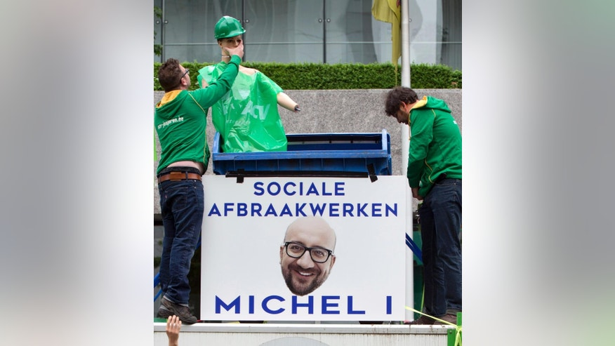 Union members put together a mannequin with a poster of Belgian Prime Minister Charles Michel under the slogan 'Social Dismantling' during a demonstration regarding labor reforms in Brussels on Tuesday, May 24, 2016. (AP Photo/Virginia Mayo)
