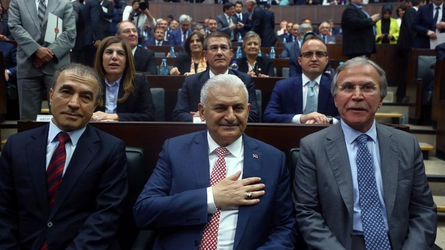 Binali Yildirim, center, who replaces the outgoing prime minister Ahmet Davutoglu, smiles to cheering lawmakers at the parliament in Ankara, Turkey, Tuesday, May 24, 2016. President Recep Tayyip Erdogan has approved a new government formed by his trusted ally who has pledged to push through constitutional reforms that would expand the powers of the presidency. (AP Photo)