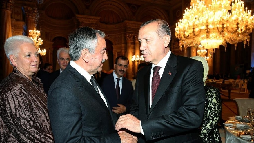 Turkey's President Recep Tayyip Erdogan, right, welcomes Turkish Cypriot leader Mustafa Akinci, center, prior to a dinner at the historical Dolmabahce Palace in Istanbul, Monday, May 23, 2016. World leaders and representatives of humanitarian organizations from across the globe are converging in Istanbul for the first World Humanitarian Summit. (Murat Cetinmuhurdar/Presidential Press Service/Pool Photo via AP)