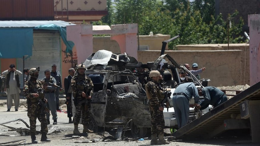 Afghanistan security forces inspect at the site of a suicide attack in west of Kabul, Afghanistan, Wednesday, May 25, 2016. A suicide bomber targeted a vehicle carrying court employees in Kabul during morning rush hour on Wednesday, killing several people, an Afghan official said. The Taliban claimed responsibility for the attack. (AP Photo/Massoud Hossaini)