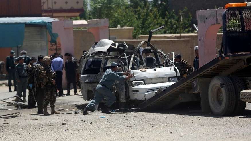 An Afghan police soldier push the destroyed vehicle on a military track at the site of a suicide attack in west of Kabul, Afghanistan, Wednesday, May 25, 2016. A suicide bomber targeted a vehicle carrying court employees in Kabul during morning rush hour on Wednesday, killing several people, an Afghan official said. The Taliban claimed responsibility for the attack. (AP Photo/Massoud Hossaini)