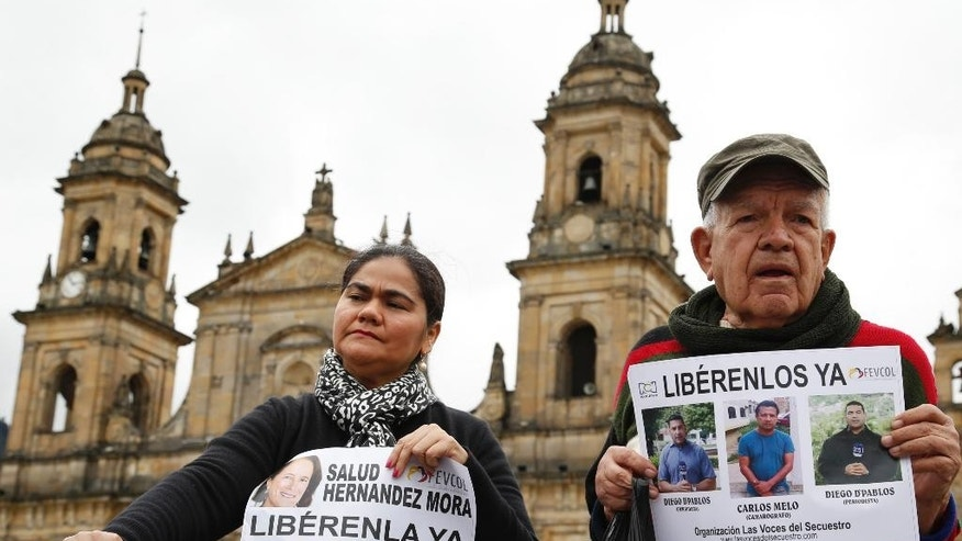 Demonstrators hold signs demanding the release of three journalists who are believed to have been taken hostage, during a sit-in in Bogota, Colombia, Wednesday, May 25, 2016. Salud Hernandez-Mora, correspondent in Colombia for Spain's El Mundo and columnist for the Bogota daily El Tiempo, as well as Diego D'Pablos and Carlos Melo, journalists at the local TV network RCN, are reported missing on the northeastern Colombia's border with Venezuela, a mountainous area dominated by leftist rebels and drug-traffickers. (AP Photo/Fernando Vergara)