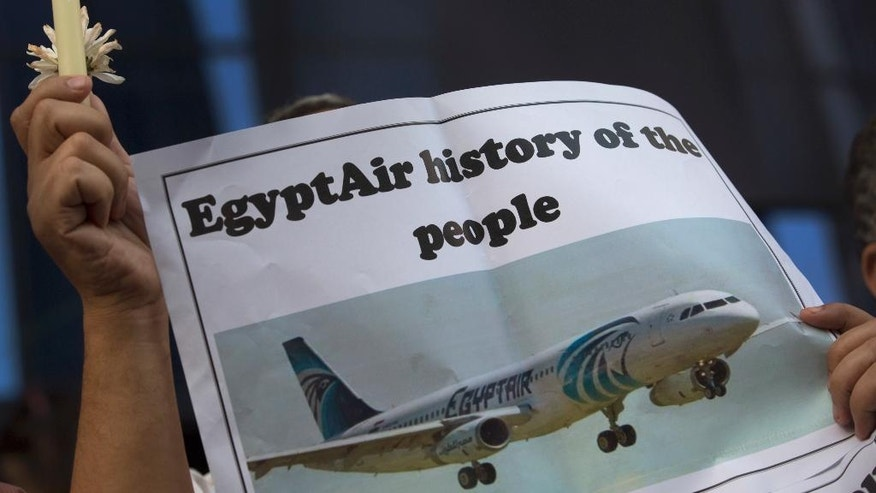 An Egyptian journalist holds a candle and a poster supporting EgyptAir during a candlelight vigil for the victims of EgyptAir flight 804 in front of the Journalists' Syndicate in Cairo, Egypt, Tuesday, May 24, 2016. The cause of Thursday's crash of the EgyptAir jet flying from Paris to Cairo that killed all 66 people aboard still has not been determined. Ships and planes from Egypt, Greece, France, the United States and other nations are searching the Mediterranean Sea north of the Egyptian port of Alexandria for the jet's voice and flight data recorders. (AP Photo/Amr Nabil)