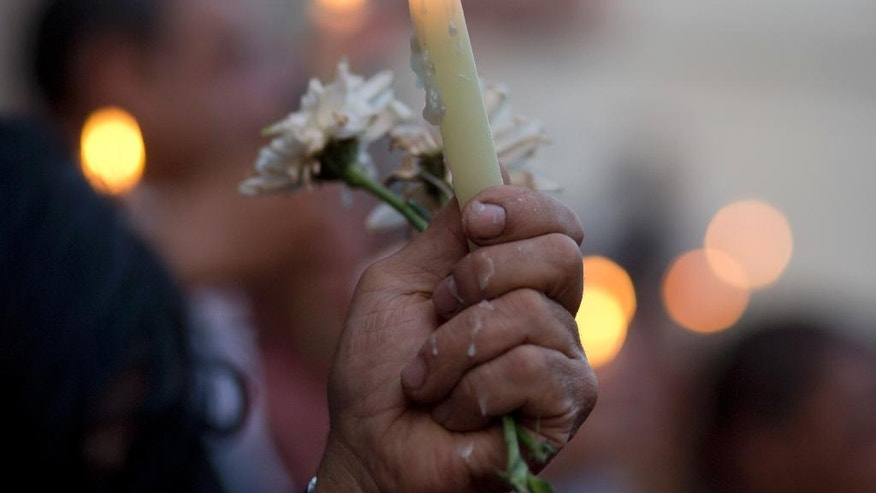 An Egyptian journalist holds a candle during a candlelight vigil for the victims of EgyptAir flight 804 in front of the Journalists' Syndicate in Cairo, Egypt, Tuesday, May 24, 2016. The cause of Thursday's crash of the EgyptAir jet flying from Paris to Cairo that killed all 66 people aboard still has not been determined. Ships and planes from Egypt, Greece, France, the United States and other nations are searching the Mediterranean Sea north of the Egyptian port of Alexandria for the jet's voice and flight data recorders. (AP Photo/Amr Nabil)