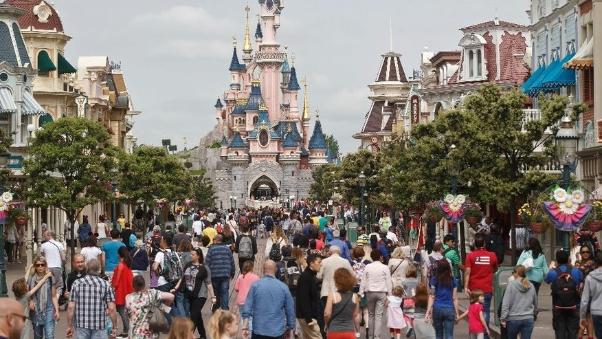 "FILE - In this May 12, 2015, file photo, visitors walk near Sleeping Beauty's Castle at Disneyland Paris, in Marne la Vallee, east of Paris. The Euro Disney group is going on trial in France, Wednesday May 25, 2016, for publishing an allegedly discriminatory job ad requesting that candidates have ""European citizenship"" to work as parade artists at its famous Disneyland Paris theme park. (AP Photo/Michel Euler, File)"