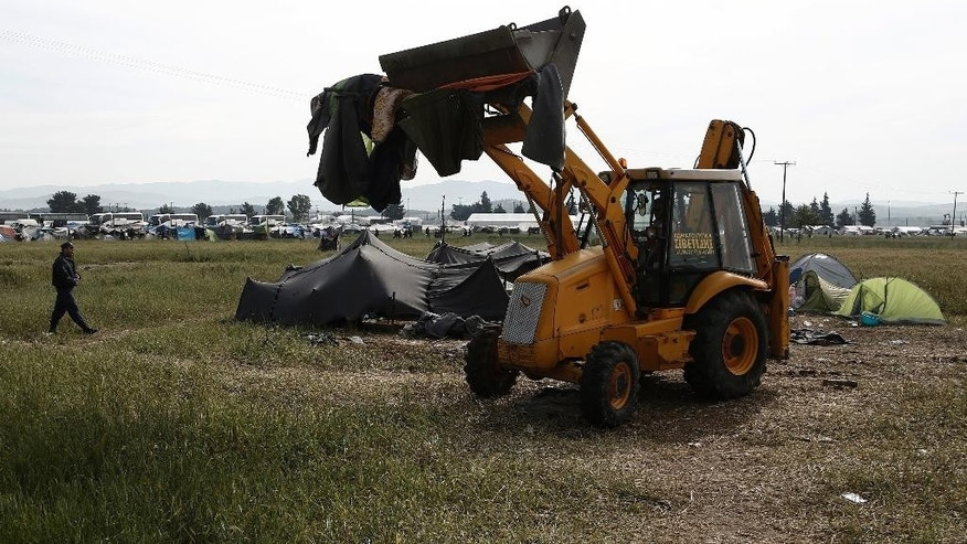 A bulldozer clears a makeshift refugee camp during a police operation at the Greek-Macedonian border near the northern Greek village of Idomeni, Tuesday, May 24, 2016.  Greek authorities sent hundreds of police into the country's largest informal refugee camp at Tuesday to support the evacuation of the Idomeni site near the Macedonian border. (Yannis Kolesidis/ANA-MPA via AP)