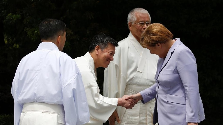 German Chancellor Angela Merkel, right, is welcomed by Shinto priests as she visits the Ise Jingu shrine in Ise, Mie prefecture, Japan Thursday, May 26, 2016, ahead of the first session of the G7 summit meetings. The leaders of the G-7 nations have arrived for a visit at Ise Jingu, the most hallowed site for Japan's indigenous Shinto religion. (Toru Hanai/Pool Photo via AP)