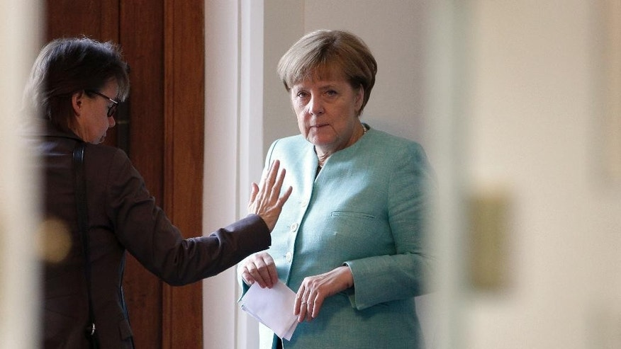 German Chancellor Angela Merkel, right, talks to her office manager Beate Baumann, left, prior to a cabinet meeting as part of a two-day retreat of the German government in Meseberg north of Berlin, Germany, Wednesday, May 25, 2016. (AP Photo/Michael Sohn)