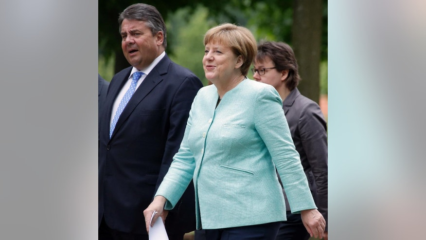 German Chancellor Angela Merkel, front right, and German Minister for Economic Affairs and Energy, Sigmar Gabriel, left, arrive for a press conference after a cabinet meeting as part of a two-day retreat of the German government in Meseberg north of Berlin, Germany, Wednesday, May 25, 2016. (AP Photo/Michael Sohn)