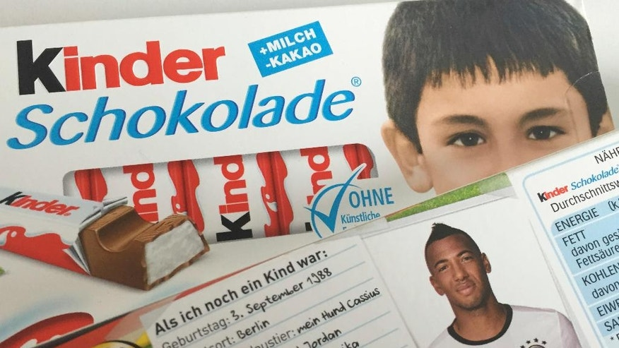 A package with a short bio of national soccer player Jerome Boateng sits on a package of a popular chocolate bar with a childhood picture of Ilkay Gundogan as they are placed on a table for a photograph in Berlin Wednesday, May 25, 2016. Candymaker Ferrero swapped the usual blond boy on its 'Kinder' bars ahead of this summer's European Championships for photos of German players as children and prompted online outrage among Germany's far right. Jerome Boateng, whose father is from Ghana, was born in Berlin and Ilkay Gundogan, whose parents are Turkish, was born in Gelsenkirchen. (AP Photo/Ferdinand Ostrop)
