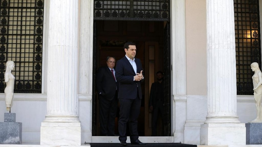 Greece's Prime Minister Alexis Tsirpas waits for the arrival of the Cypriot President Nicos Anastasiades at the Maximos Mansion in Athens, Wednesday, May 25, 2016. Greece has won an essential batch of bailout funds from international creditors following agreement among the 19 eurozone finance ministers and can start looking forward to debt relief in the future. (AP Photo/Thanassis Stavrakis)