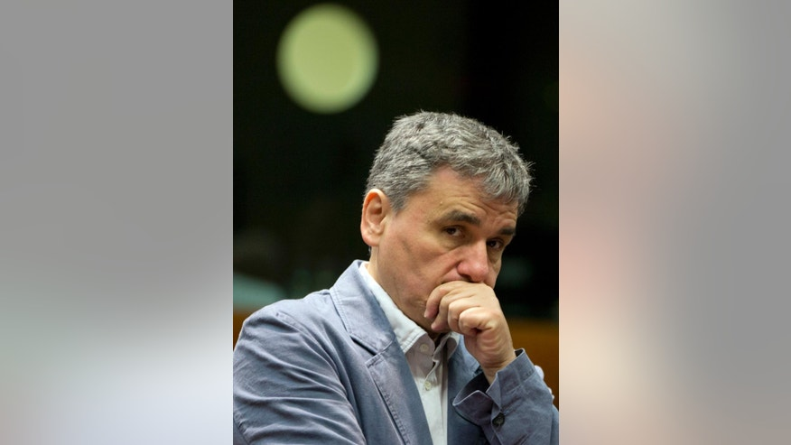 Greece's Finance Minister Eucleidis Tsakalotos waits for the start of a meeting of EU finance ministers in Brussels on Wednesday, May 25, 2016. Eurozone finance ministers struck a deal early Wednesday clearing the way for Greece to access a fresh round of bailout funds, while also laying out debt relief measures aimed at securing the involvement of the International Monetary Fund, or IMF. (AP Photo/Virginia Mayo)