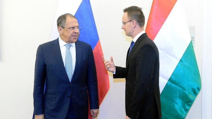 Hungarian Minister of Foreign Affairs and Trade Peter Szijjarto, right, welcomes Russian Foreign Minister Sergey Lavrov in the Ministry of Foreign Affairs and Trade in Budapest, Hungary, Wednesday, May 25, 2016. (Tamas Kovacs/MTI via AP)