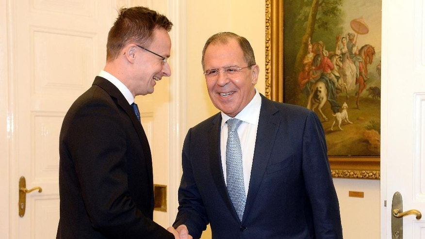 Hungarian Minister of Foreign Affairs and Trade Peter Szijjarto, left, welcomes Russian Foreign Minister Sergey Lavrov in the Ministry of Foreign Affairs and Trade in Budapest, Hungary, Wednesday, May 25, 2016. (Tamas Kovacs/MTI via AP)