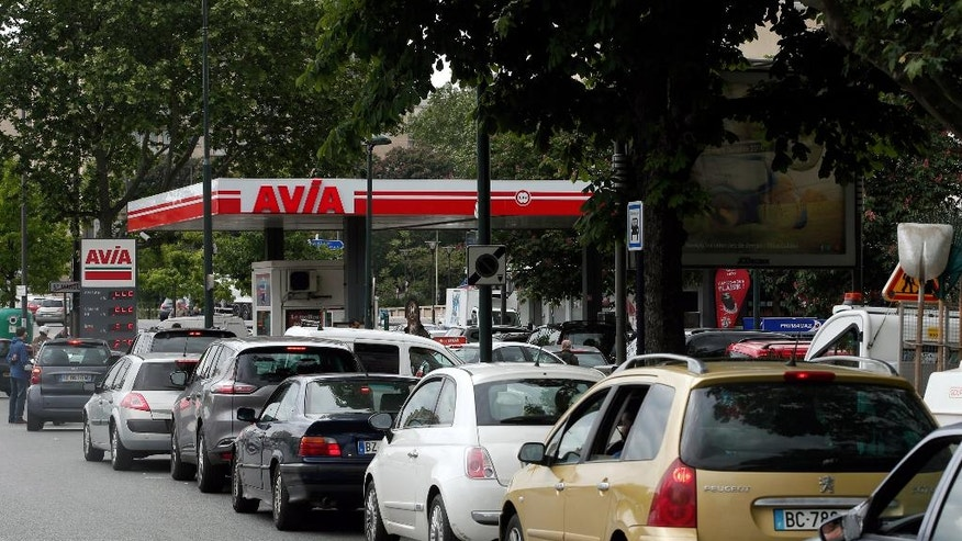 Drivers line up as they wait to buy gas in a station, in Paris, Tuesday, May 24, 2016.  A two-month protest movement against a bill weakening France's famed worker protections reached a new level this week as fuel industry workers joined in. Strikes have spread to all eight of France's refineries, and one in five gas stations are now dry or running low. (AP Photo/Thibault Camus)