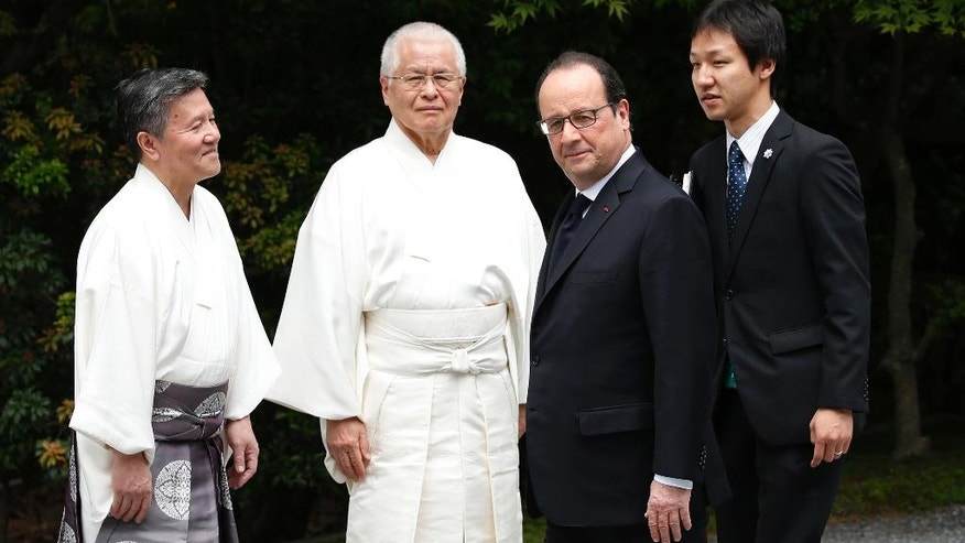 French President Francois Hollande, second right, is welcomed by a Shinto priest as he walks on the Ujibashi bridge while visiting Ise Grand Shrine in Ise, Mie prefecture, Japan, May 26, 2016, ahead of the first session of the G7 summit meetings. The leaders of the G-7 nations have arrived for a visit at Ise Jingu, a shrine that is the most hallowed site for Japan's indigenous Shinto religion. (Toru Hanai/Pool Photo, via AP)