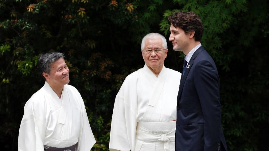 Canadian Prime Minister Justin Trudeau, right, is welcomed by Shinto priests as he visits Ise Jingu shrine in Ise, Mie prefecture, Japan, Thursday, May 26, 2016, ahead of the first session of the G7 summit meetings.The leaders of the G-7 nations have arrived for a visit at Ise Shrine, the most hallowed site for Japan's indigenous Shinto religion. (Toru Hanai/Pool Photo via AP)
