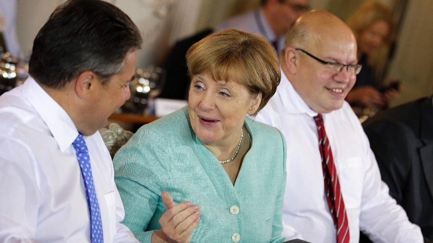 From left, German Minister for Economic Affairs and Energy, Sigmar Gabriel, German Chancellor Angela Merkel and Peter Altmaier, Head of the Federal Chancellery and Federal Minister for Special Tasks chat at the beginning of a cabinet meeting as part of a two-day retreat of the German government in Meseberg north of Berlin, Germany, Wednesday, May 25, 2016. (AP Photo/Michael Sohn)