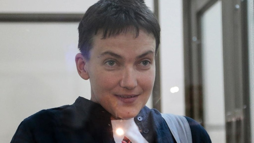 FILE - In this Monday, March 21, 2016 file photo, Ukrainian pilot Nadezhda Savchenko smiles to journalists from a glass-covered cage in court in Donetsk, Rostov-on-Don region, Russia. A lawyer for one of two Russian servicemen jailed in Ukraine says the groundwork is being laid for a possible exchange with Savchenko, who is imprisoned in Russia. Lawyer Valentin Rybin told the state news agency Tass on Wednesday, May 25, 2016, that both Russians have submitted a petition for a pardon to Ukrainian President Petro Poroshenko. (AP Photo/Ivan Sekretarev, File)