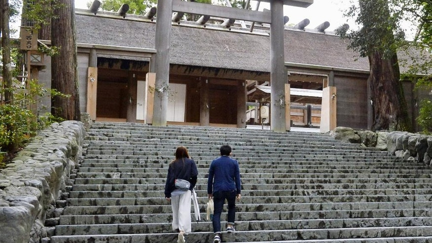 In this May 11, 2016 photo, a couple climbs the steps of Ise Grand Shrine, or Ise Jingu, in Ise city, central Japan. The Shinto shrine that Japanese Prime Minister Shinzo Abe is taking his Group of Seven counterparts to on Thursday, May 26, 2016, is no ordinary shrine. Ise JIngu is actually a cluster of 125 shrines around the two most important sanctuaries, the Inner and Outer Shrines and is considered the holiest spot in Japan. (Yoshiaki Sakamoto/Kyodo News via AP) JAPAN OUT, MANDATORY CREDIT