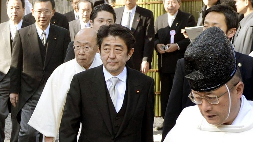 FILE - In this Jan. 4, 2013, file photo, Japanese Prime Minister Shinzo Abe, center, is led by a Shinto priest during his visit to Ise Grand Shrine, or Ise Jingu, in Ise city, central Japan. The Shinto shrine that Abe is taking his Group of Seven counterparts to on Thursday, May 26, 2016, is no ordinary shrine. (Kyodo News via AP, File) JAPAN OUT, MANDATORY CREDIT