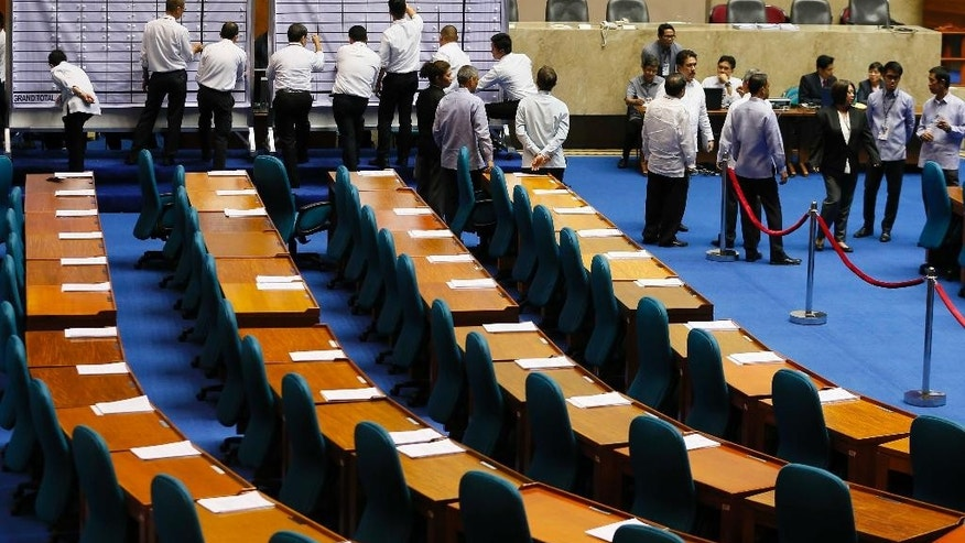 Philippine House and Senate election tribunal staff prepare the tally board before the official count of votes cast in the May 9 presidential election begins Wednesday, May 25, 2016 in the Lower House in suburban Quezon city, northeast of Manila, Philippines. The Philippine Congress on Wednesday started the official count, though confirmation of Rodrigo Duterte's apparent victory may be slowed by disputes in the more closely fought vice presidential race. (AP Photo/Bullit Marquez)