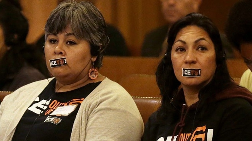 Two women calling for San Francisco to maintain its strict sanctuary protections for people who are in the country illegally wear tape over their mouths while listening to speakers at a Board of Supervisors meeting at City Hall in San Francisco, Tuesday, May 24, 2016. San Francisco supervisors are scheduled to vote on a proposal Tuesday that spells out when law enforcement can turn over criminal suspects to federal immigration authorities if they are charged with a violent crime and have been convicted of a violent crime within the last seven years. (AP Photo/Jeff Chiu)