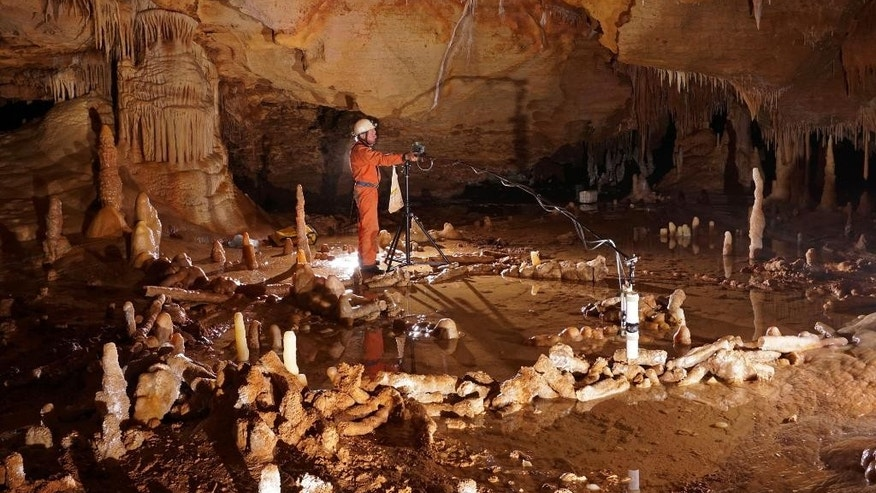 In this undated image released by CNRS on Wednesday May 25, 2016 a scientist takes measurements of stone rings inside a cave on Bruniquel in France. Scientists say that a pair of mysterious stone rings found deep inside a French cave was probably built by Neanderthals about 176,500 years ago, proving that our ancient cousins were capable of more complex behavior than previously thought. The structures were made from hundreds of column-shaped mineral deposits, called stalagmites, that were chopped to a similar length and laid out in two oval patterns up to 40 centimeters (16 inches) inches high. (Etienne Fabre/CNRS via AP)