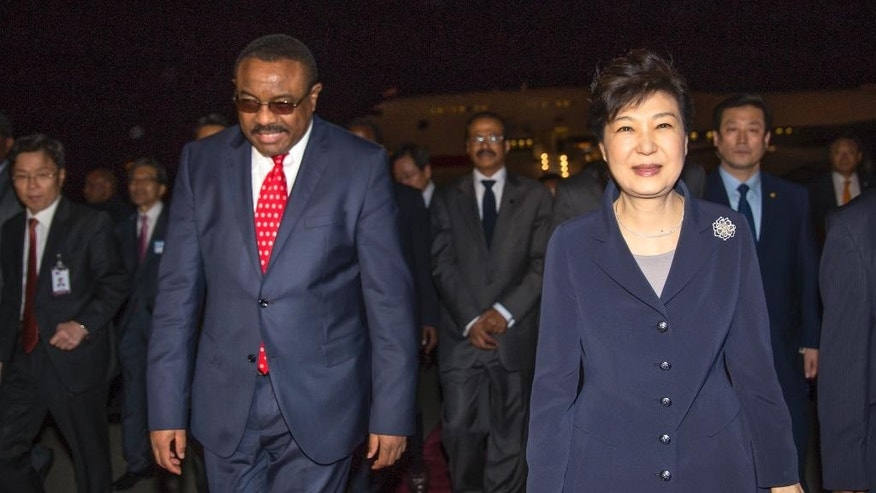 Ethiopia's Prime Minister Hailemariam Desalegn, left, walks with South Korea's President Park Geun-hye, right, as she arrives at the airport in Addis Ababa, Ethiopia, Wednesday, May 25, 2016. Geun-hye arrived in the Ethiopian capital on Wednesday evening at the start her three-nation visit to Africa, and is also slated to visit Kenya and Uganda to hold bilateral talks. (AP Photo/Mulugeta Ayene)