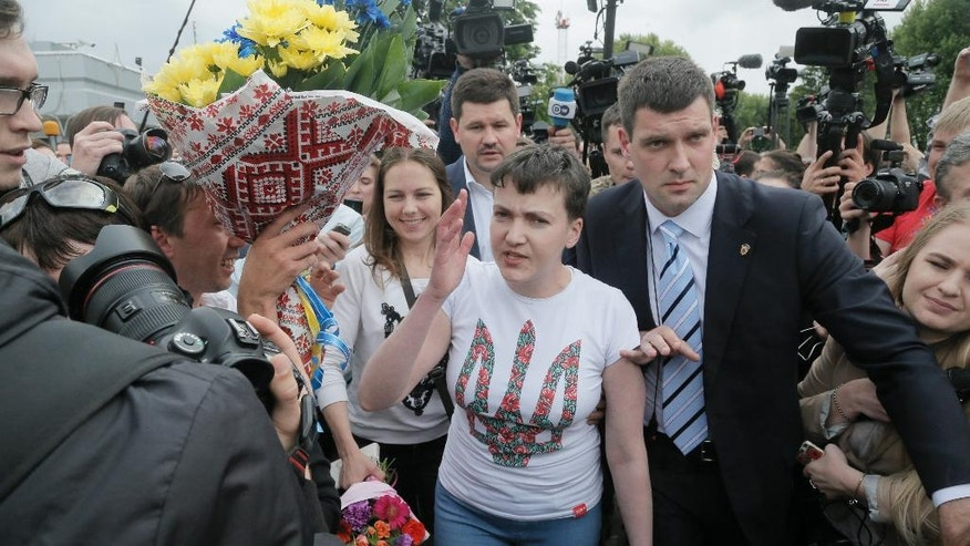 Ukrainian jailed pilot Nadezhda Savchenko, center, speaks to the media as she and her sister Vera, left of her, walk together upon her arrival at Boryspil airport outside Kiev, Ukraine, Wednesday, May 25, 2016. Russia has released jailed pilot Nadezhda Savchenko, as part of a swap for two Russian servicemen imprisoned in Ukraine. (AP Photo/Efrem Lukatsky)
