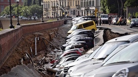 Cars are engulfed by a chasm which opened along Arno river near the Ponte Vecchio Old Bridge, in Florence, Italy, Wednesday,  May 25, 2016.  According to reports, the collapse occurred early in the morning and is caused by the rupture of an acqueduct. No one was injured. (Maurizio degl'Innocenti/ANSA via AP)