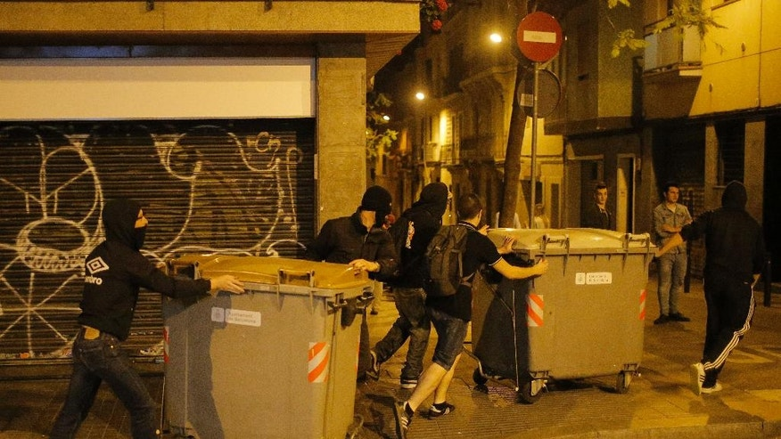 Protestors move garbage containers during a demonstration in support of squatters in Barcelona, Spain, Wednesday, May 25, 2016. Protesters supporting squatters in Barcelona clashed with police for the third night in a row. The activists want squatters allowed back inside a vacant bank branch they occupied for years before they were evicted. (AP Photo/Manu Fernandez)