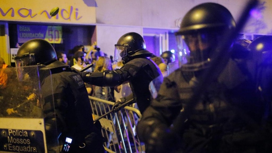 Riot police use their batons to disperse demonstrators in support of squatters in Barcelona, Spain, Wednesday, May 25, 2016. Protesters supporting squatters in Barcelona clashed with police for the third night in a row. The activists want squatters allowed back inside a vacant bank branch they occupied for years before they were evicted. (AP Photo/Manu Fernandez)
