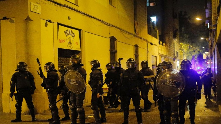 Riot police take position during a demonstration in support of squatters in Barcelona, Spain, Wednesday, May 25, 2016. Protesters supporting squatters in Barcelona clashed with police for the third night in a row. The activists want squatters allowed back inside a vacant bank branch they occupied for years before they were evicted. (AP Photo/Manu Fernandez)