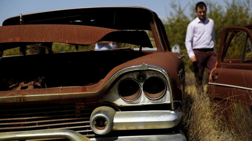British base official Ian Brayshaw walks past an abandoned rusted U.S made car at the British military base in Episkopi near the southern coastal city of Limassol in the Mediterranean island of Cyprus, on Wednesday, May 25, 2016.  The cars were abandoned by Turkish Cypriot owners inside a British military base amid the confusion of a war 42 years ago that cleaved Cyprus along ethnic lines.  Now base authorities are hoping to reawaken the interest of owners to reclaim these vehicles before their disposal starts next year. (AP Photo/Petros Karadjias)