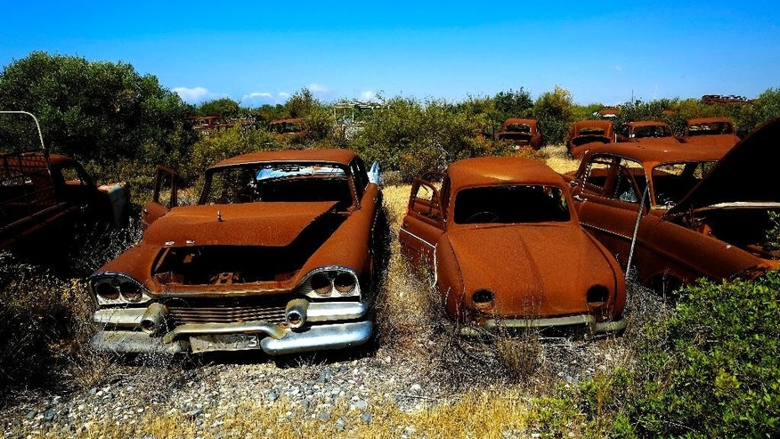 Rusted cars abandoned at the British military base in Episkopi near the southern coastal city of Limassol in the Mediterranean island of Cyprus, on Wednesday, May 25, 2016.  The cars were abandoned by Turkish Cypriot owners inside a British military base amid the confusion of a war 42 years ago that cleaved Cyprus along ethnic lines.  Now base authorities are hoping to reawaken the interest of owners to reclaim these vehicles before their disposal starts next year. (AP Photo/Petros Karadjias)